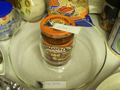 A jar of Newman's Own salsa in the middle of a glass chip bowl. On the lid is a small handwritten note with Salsa written on it. The chip bowl has a note that says Chip/Salsa