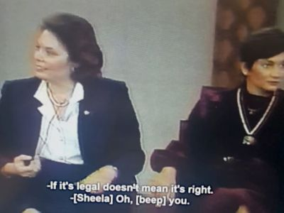 A white woman in a white blouse and dark blue blazer looks away from Sheela, seated on the right. The text reads: If it's legal doesn't mean it's right. Sheela: Oh, beep you.