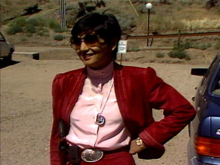 Sheela, a small woman with dark, short hair smiles with one hand on her hip. She's wearing oversized tinted glasses, burgandy jacket, pink blouse, a large silver buckle. Around her neck is a long, beaded pendant holding a portrait of Bhagwan.