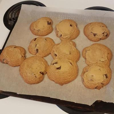 Ten chocolate chip cookies on a baking sheet that have mostly melted so that they're touching each other.