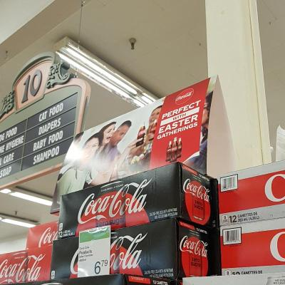 A display sign sits on top of boxes of Coca-Cola. The sign features a diverse group of friends holding up bottles of coke. The sign reads: Perfect with Easter Gatherings.