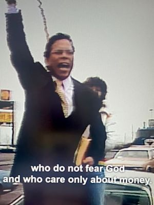 A middle-aged man with one arm raised is yelling. He is wearing a dark suit and a yellow patterned tie. The caption reads: who do not fear God and who care only about money.