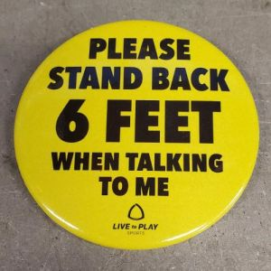 A yellow button reads PLEASE STAND BACK 6 FEET WHEN TALKING TO ME.