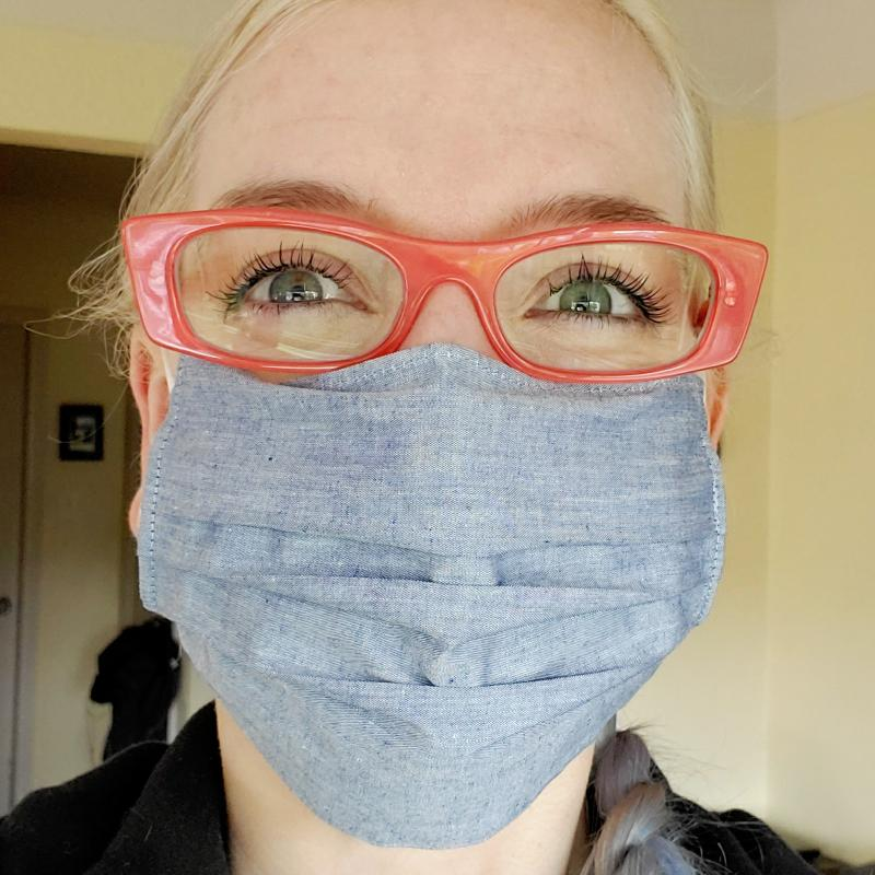 I'm looking at the camera with happy eyes. I am wearing orange eyeglasses and a light blue fabric mask.