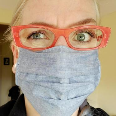 One eyebrow is slightly raised while I have a pained look in my eyes. I am wearing orange eyeglasses and a light blue mask.