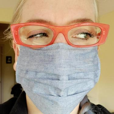 Giving the side-eye. My eyebrows are relaxed. Orange eyeglasses and blue face mask makes yet another appearance.