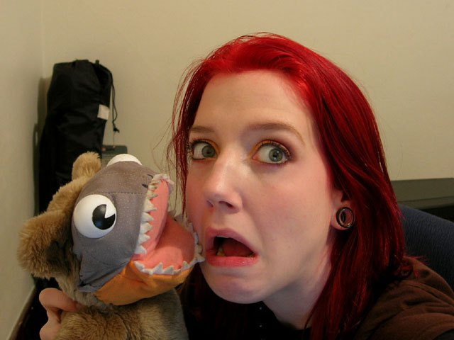An old photo of me from when I had bright red hair. I am holding up the aforementioned piranha-faced bear plushy. My mouth is open.