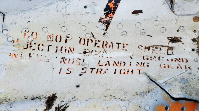 A crumpled metal panel reads DO NOT OPERATE SHELL EJECTION (word is illegible)  GROUND UNLESS NOSE LANDING GEAR IS STRAIGHT.