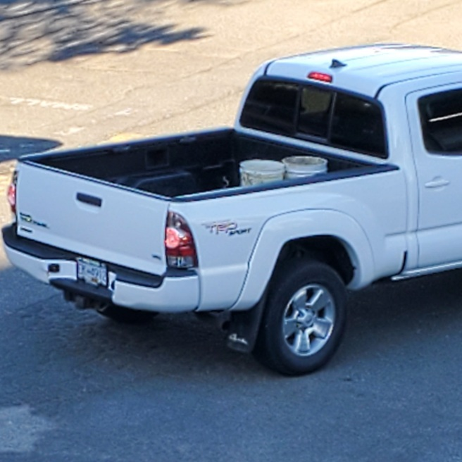 The bed of a white Toyota Tacoma pickup truck. Two dirty white buckets are visible in the bed. The brake lights are on, and the license plate is blurry, but the number appears to be EK 912.