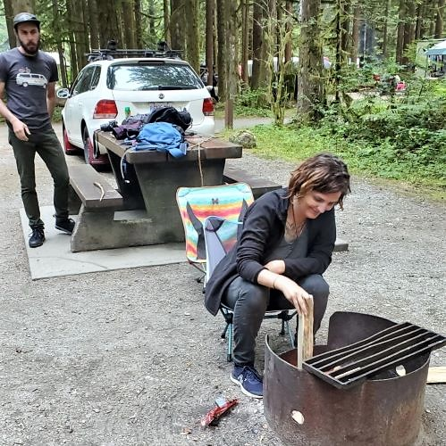 Zoee is seen in the foreground putting kindle in a fire pit. She has short brown hair and is wearing a black fleece jacket, black jeans, and navy blue New Balance sneakers. Yann stands to the left in the background scoping Zoee's fire starting technique. He is wearing a black hat, a dark grey t-shirt with a white van on it and dark pants.