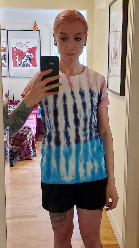 Laura is wearing a tri-coloured tie-dyed t-shirt with three blocks of colours interrupted by vertical blank spaces. She is looking at her phone's screen, looking slightly dejected.