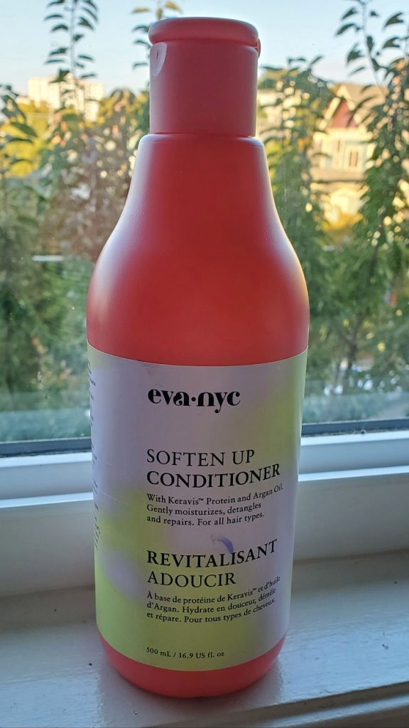 A pink bottle of conditioner with a label that reads: Eva NYC  Soften Up Conditioner  With Keravis Protein and Argan Oil. Gently moisturizes, detangles, and repairs. For all hair types.
