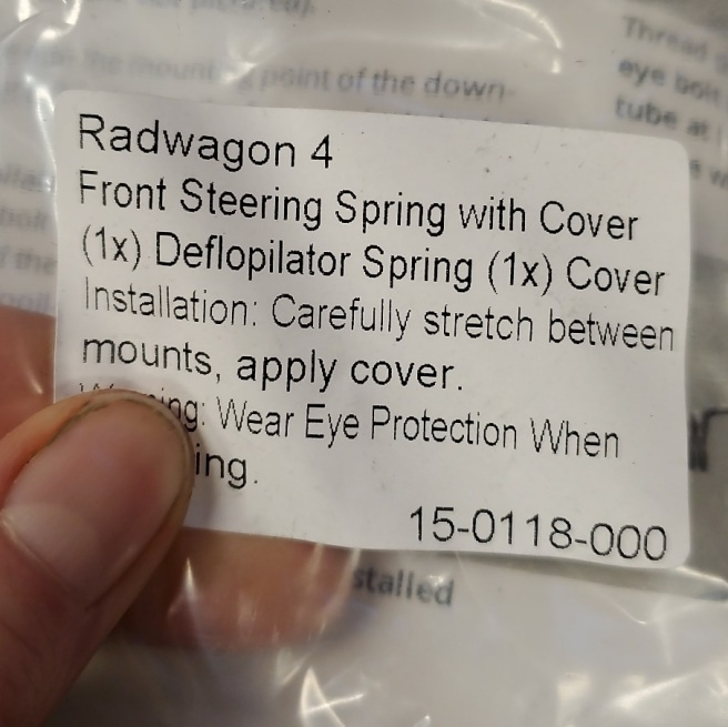Printed label reads: Radwagon 4 Front Steering Spring with Cover (1x) Deflopilator Spring (1x) Cover Installation: Carefully stretch between mounts, apply cover. Warning: Wear Eye Protection when... (the last words is blocked out by my thumb.)