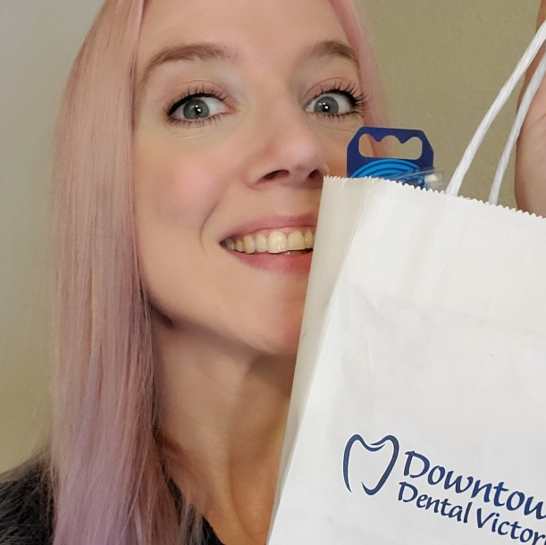 I'm holding up my dental goody bag with a smile.