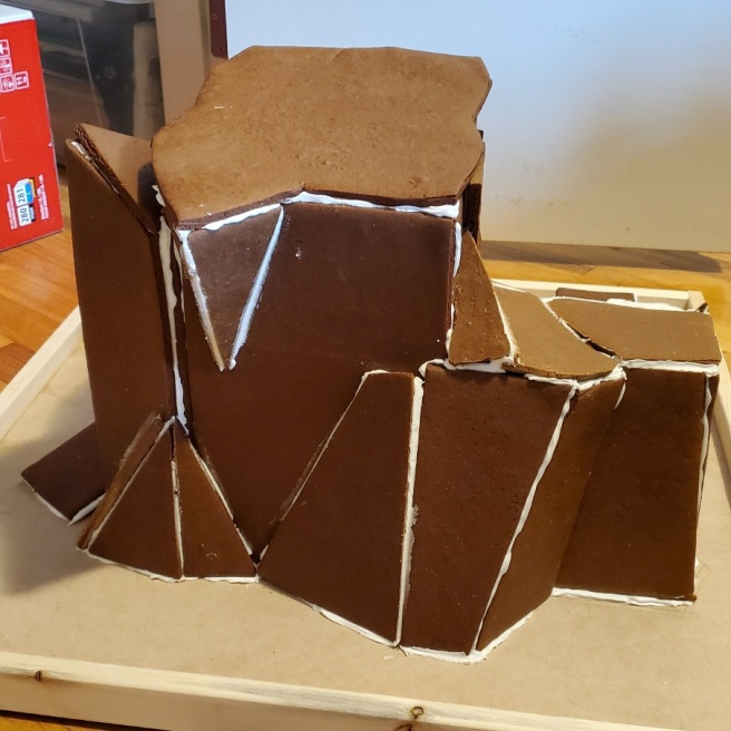 """Irregularly-shaped slabs of gingerbread rests atop a particleboard platform bordered by a 1.5"""" high strips of wood."""