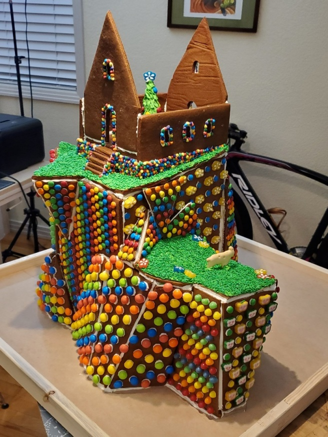 A partially decorated gingerbread structure shows a Christmas tree inside a house before the roof went on.