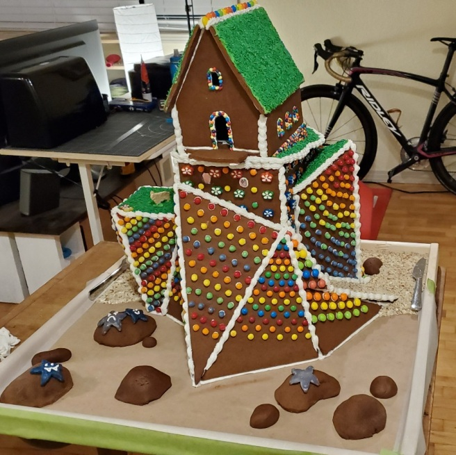 The front of a partially decorated gingerbread structure shows mounds of gingerbread arranged to resemble boulders. On three of the boulders are anthropomorphic starfish.