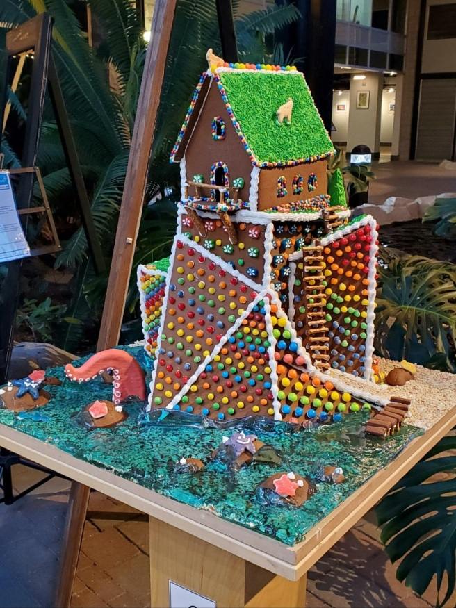 The completed gingerbread creation on display. The pier, ladder, boulders, tentacle, and rooftop goats are visible.