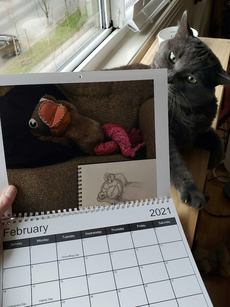 A calendar showing a plushie with the face of a piranha, body of a teddy bear, and legs of a pink frog lying on the couch with a sketchbook in front. The calendar is turned to the month of February. Behind the calendar is a curious grey cat.