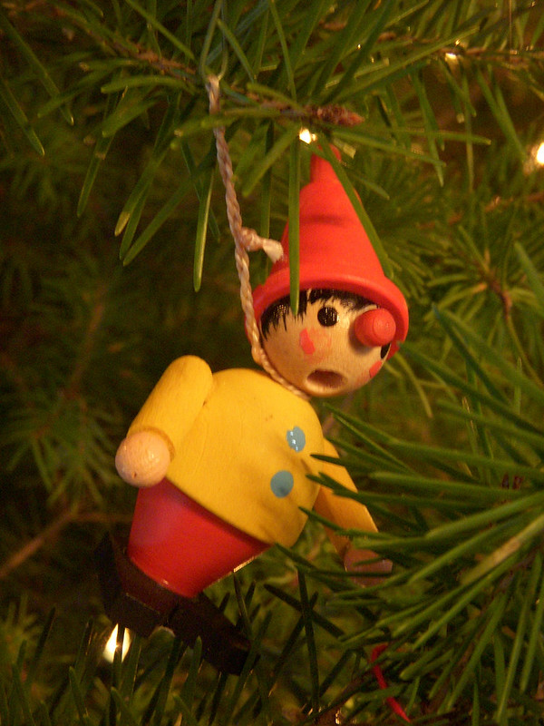 A wooden elf ornament with a hole for its mouth. It hangs from a branch by its neck.