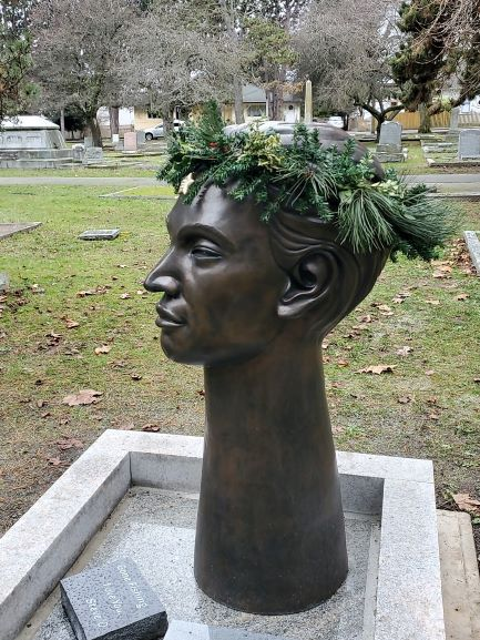 Side profile of a long-necked headstone wearing a crown made of spruce boughs.