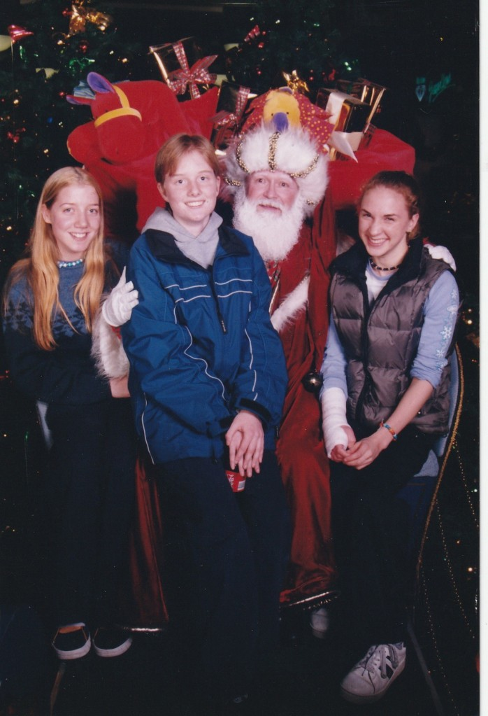 Three teenagers and a mall Santa. I'm on the left, dressed in dark blue. My hair is long, blonde and parted in the middle. Alana is int he middle, wearing a blue snowboarding jacket over a grey hoodie. She has short dark blonde hair. Erin is on the right wearing a puffy vest over a light blue baseball shirt. Her shirt sleeves are rolled up and reveals an arm in a plaster cast.