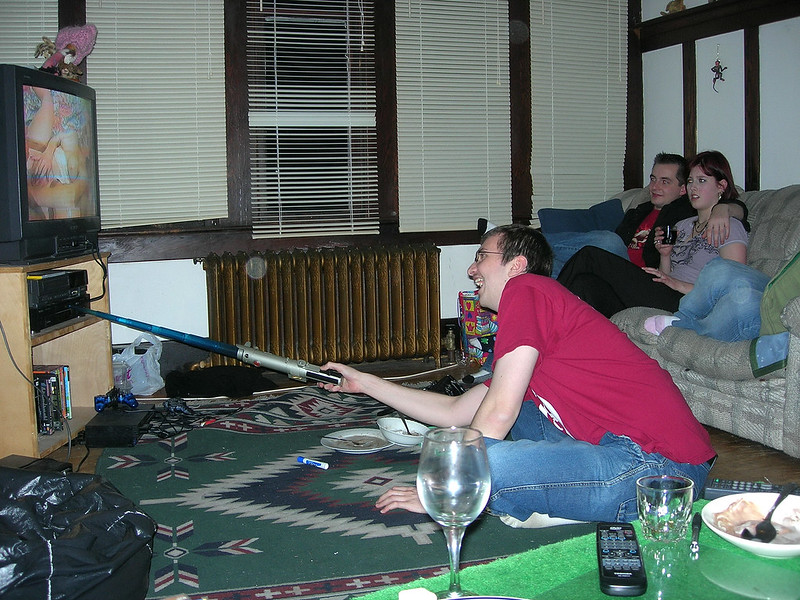 A lauging man in a burgandy t-shirt uses a collapsible light saber to reach the buttons on a VCR. On the TV monitor, a pornographic actor has her legs spread with one hand on her muff. Across from the tv is a heterosexual couple: the lady has a disturbed look on her face.