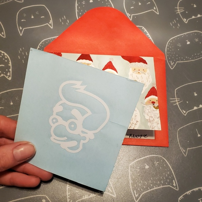 A white Milhouse decal in front of a Santa-face print Christmas card laying on top of a red envelope.