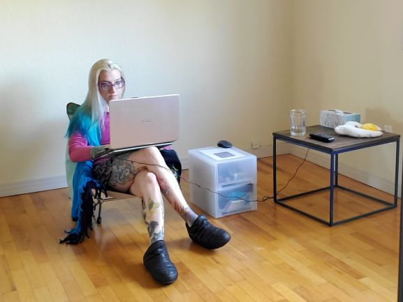 I am seated cross-legged on a camping chair with my laptop balanced on my right leg. A plastic storage drawer is next to me. Next to the storage drawer is a desk with glass of water, tv remote, tissue box and a plush fried egg on top.