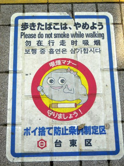 "A sign in Japanese that also has an English translation. The translation reads, ""Please do not smoke while walking."" The illustration features a cartoon cloud of smoke coming from the end of a lit cigarette. The grinning cloud of smoke is giving a thumbs-up."