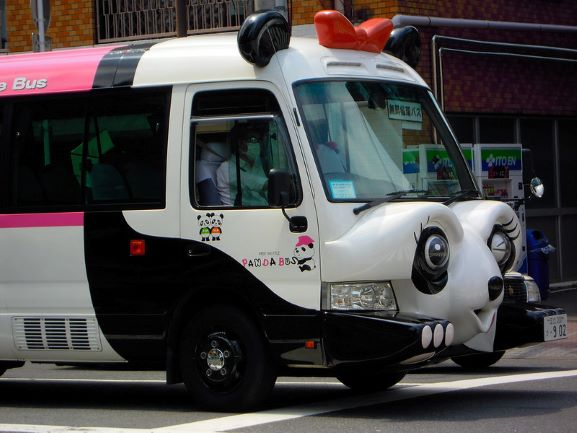 The front of a bus modelled to look like a winking cartoon panda. The panda has a red bow between its ears.