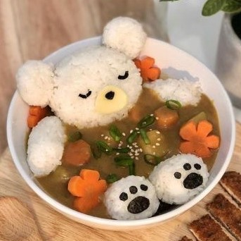Rice balled together and arranged inside a bowl to resemble a sleeping bear relaxing in a bowl of broth. The carrots have been cut to resemble cherry blossoms.