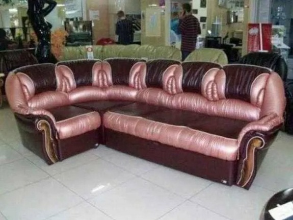 A shiny pink and maroon sectional sits in the middle of what appears to be a furniture store. The crevices of the cushions look vaginal.