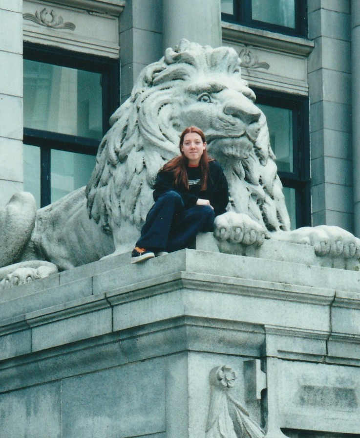 Young Laura with long, brown hair leans against the arm of a large lion sculpture. She is wearing a black jacket over a black shirt and wide-legged dark blue pants. The thick white soles of her orange and dark blue Airwalks are partially visible.