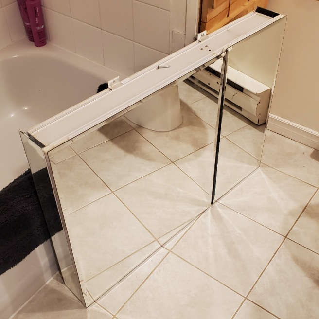 A large mirrored medicine cabinet rests on the floor in front of the bathtub.