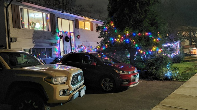 A two-storey house is decked out in Christmas decorations. Two vehicles are parked in the driveway.