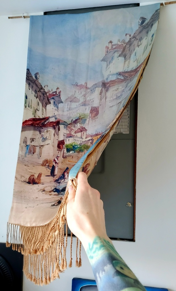 A wall tapestry featuring a painting of an old European seaside town being lifted out of the way to show the circuit breaker box.