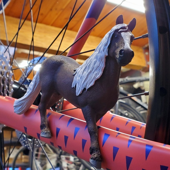 A brown toy horse with white mane and tail straddles the coral drive side chainstay of a bike. There is also a metallic blurple pattern of triangles painted on the chainstay.