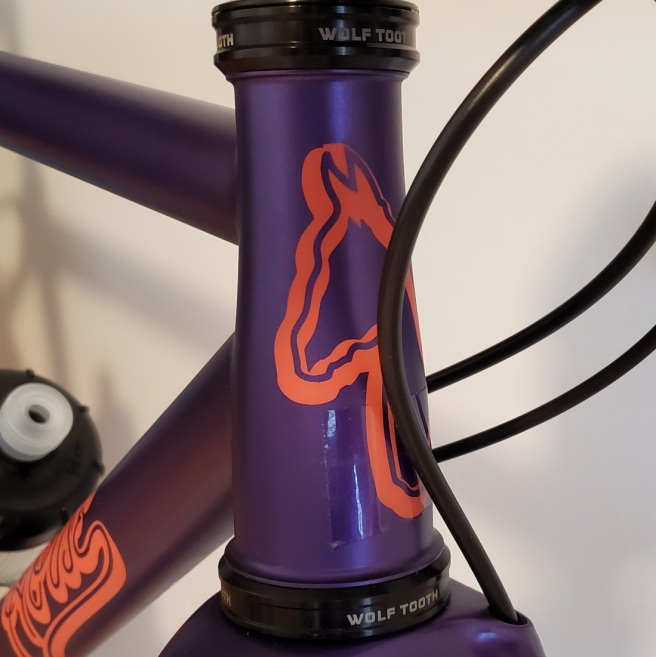 Close up of the tapered head tube with the horse logo painted on front. A piece of clear tape can be seen on the lower part of the head tube.