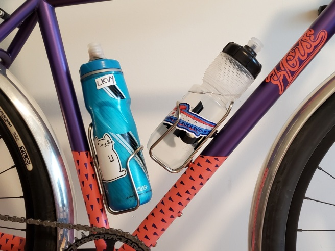 The middle of the bike frame showing the positioning of the bottle cage mounts The blue bottle on the seat tube has a white cat decal on it. The clear bottle on the downtube has a partially obscured decal of an oarfish.